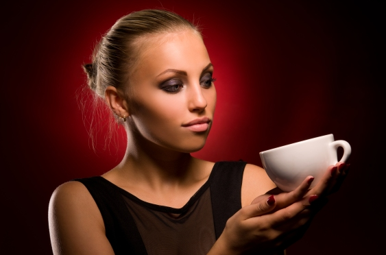 portrait of sexy girl with aggressive makeup and white cup in hand, on a black and red background